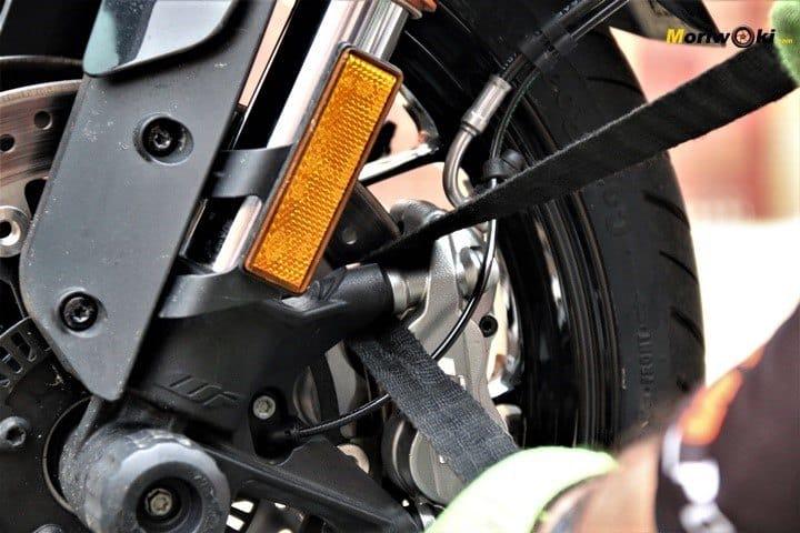 Pasando la cincha por la pinza para atar la moto al remolque