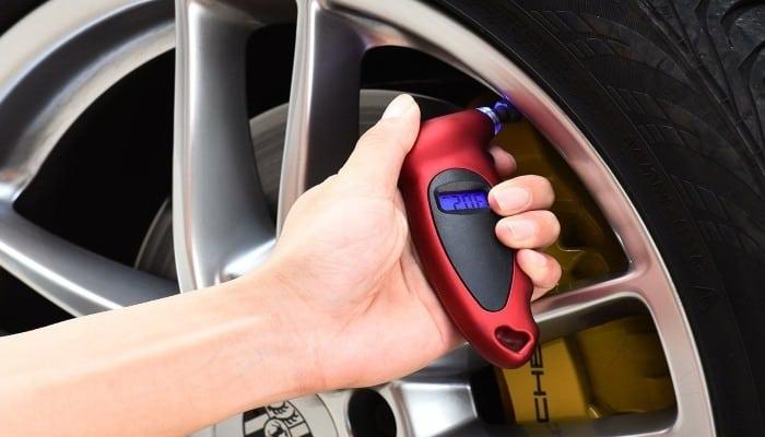 mujer utilizando el manómetro para medir la presión de su neumático