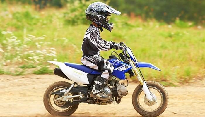 niño montando en una moto de color azul