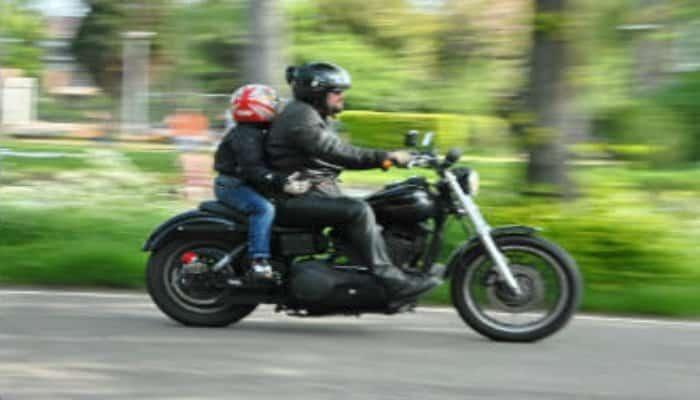 niño montado con un adulto en una moto negra