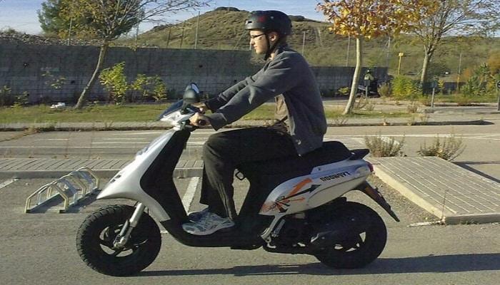 conduciendo un ciclomotor gris