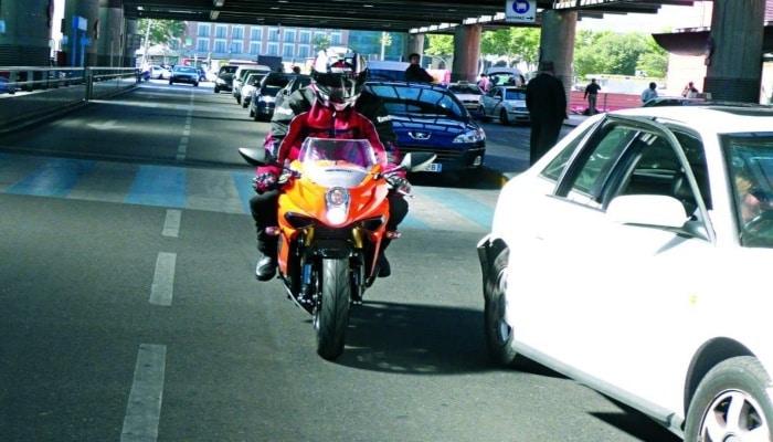 moto detrás de coche blanco