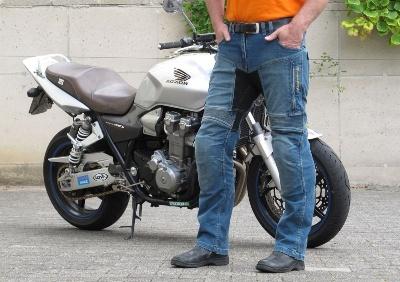 motorista con pantalones de verano delante de una moto gris